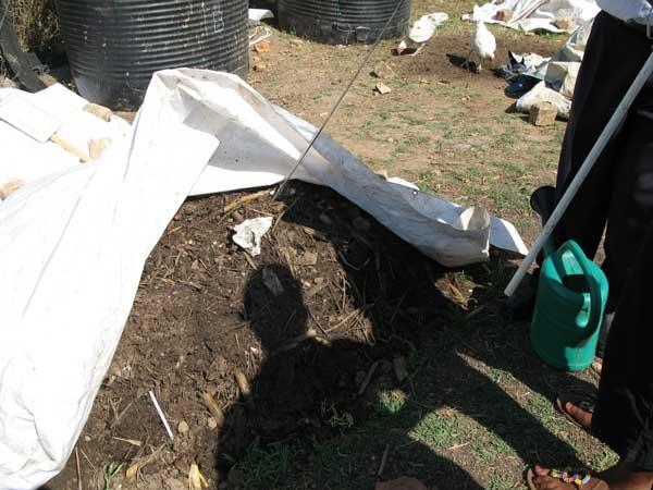 compost pile under a tarp