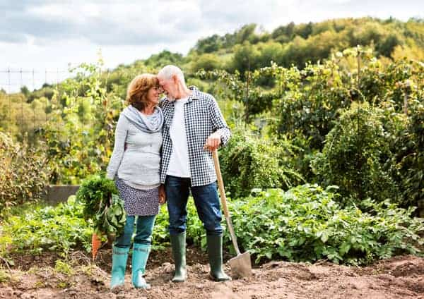 old couple with heads together in the garden