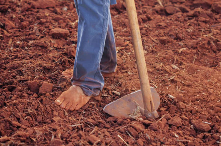 man with bare feet and garden matock