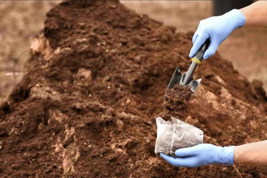 placing soil into bag with trowel