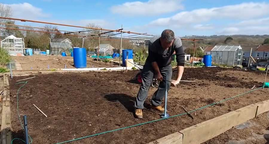 Tony O'Neill screwing in ground anchors to his new northern polytunnel