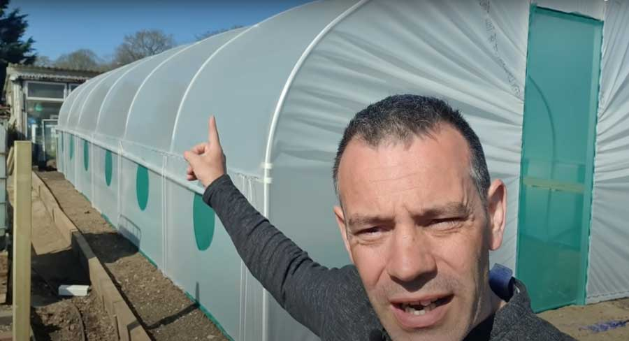 Tony O'Neill pointing at his Northern Polytunnel