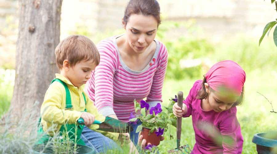 lady and 2 children gardening