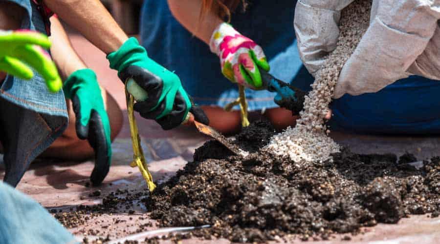 many hands mixing potting soil