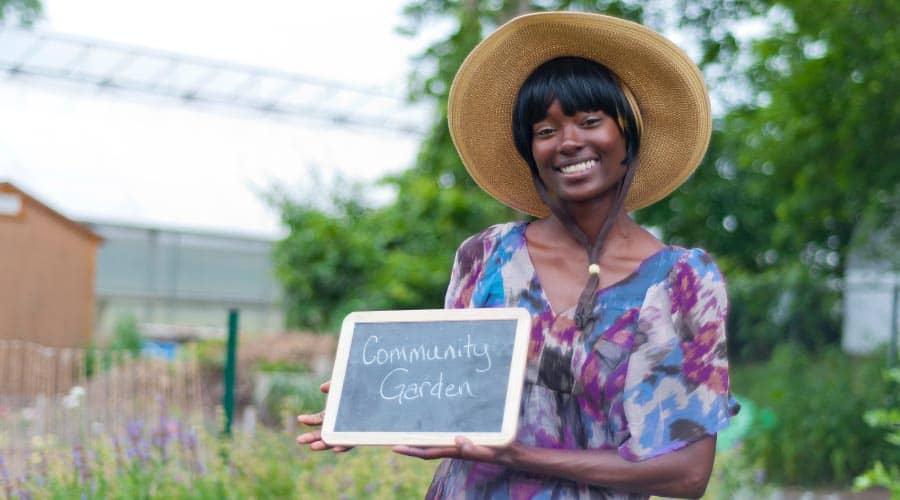 lady holding community garden sign