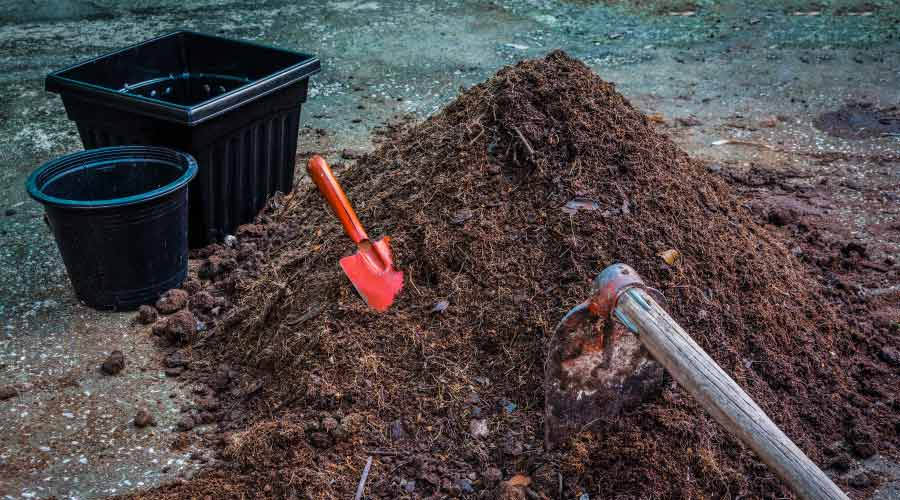 pile of compost with red trowel