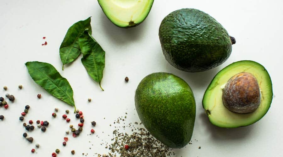 avocados on white table with seeds and leaves