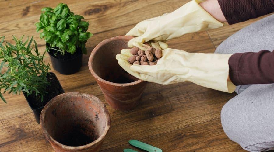 placing clay balls into a clay pot