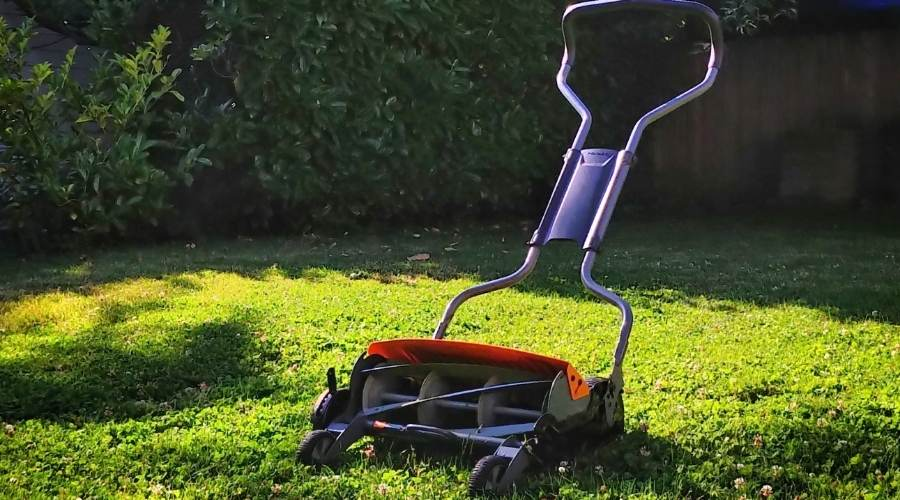 A banner picture of a non-descript reel mower in a yard