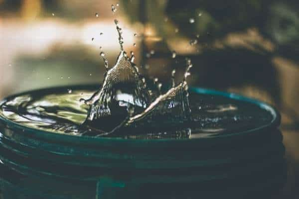 A picture of a water droplet splashing on a stack of coins