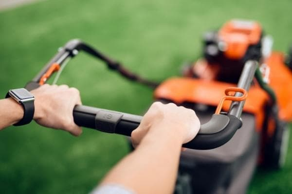 image of hands on lawn mower